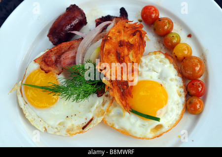 Le petit-déjeuner, une assiette d'œufs au plat, du bacon, des saucisses et tomates Banque D'Images