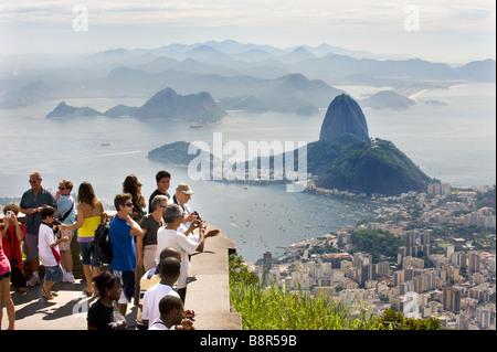 Les touristes VOIR RIO DE JANEIRO À PARTIR DE LA COLLINE DU CORCOVADO, CI-DESSOUS LE CHRIST RÉDEMPTEUR STATUE en Banque D'Images