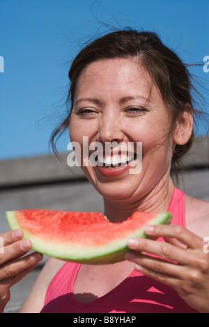 Une femme manger un melon d'eau de la Suède. Banque D'Images