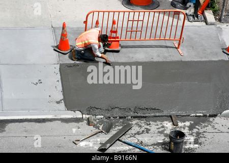 Le lissage de l'homme un trottoir de béton humide fraîchement coulé.