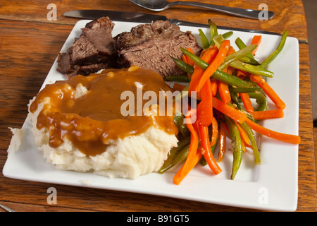 Purée de pommes de terre, sauce, rôti avec des haricots verts et la julienne de carottes sur une plaque blanche Banque D'Images