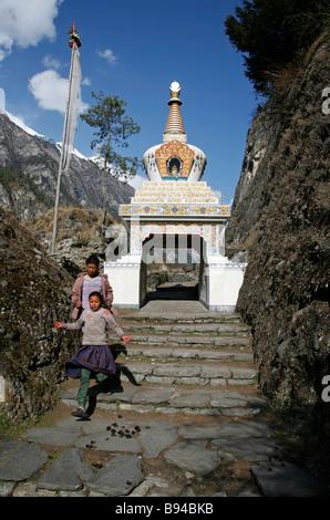 Le Népal Annapurna 21 mars 2008 enfants descendant des escaliers stupa bouddhiste passé à l'entrée du village sur Banque D'Images