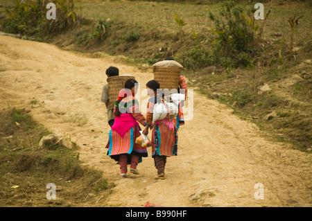Des couples Hmong fleurs colorées accueil marche de marché en cau fils près de Bac Ha Vietnam Banque D'Images