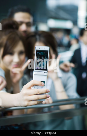 Jeunes amis taking self-portrait with cell phone, focus on cell phone Banque D'Images