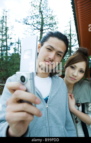 Jeune couple photographing selves with cell phone Banque D'Images