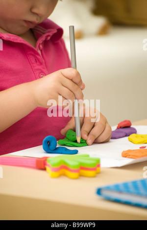 Petite fille façonner l'argile colorée avec crayon, portrait Banque D'Images