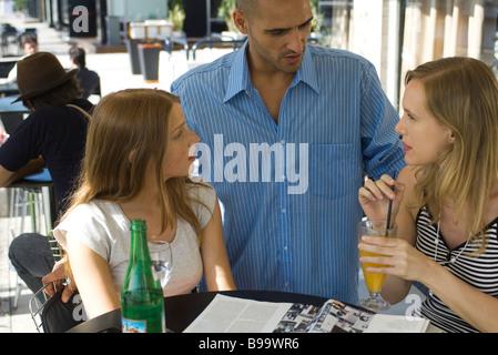 L'homme parlant à deux jeunes femmes at outdoor cafe Banque D'Images