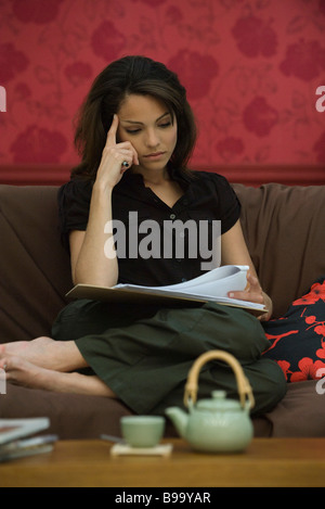Young woman reading document sur canapé Banque D'Images