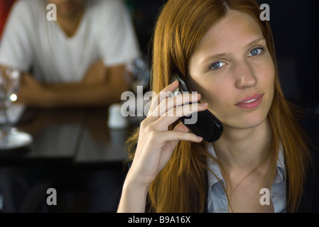 Woman holding cell phone, smiling at camera Banque D'Images