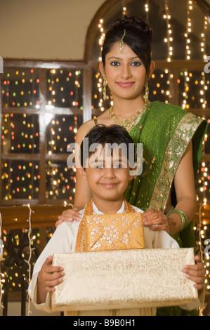Femme avec son fils holding Diwali gifts and smiling