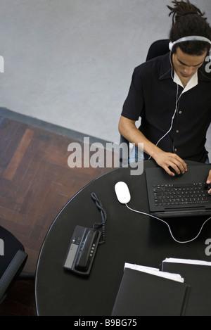 L'homme travaillant à l'ordinateur portable, l'écoute au casque, overhead view