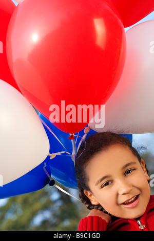 Une belle jeune fille de race mixte à très heureux avec son gros tas de ballons bleu et blanc rouge Banque D'Images