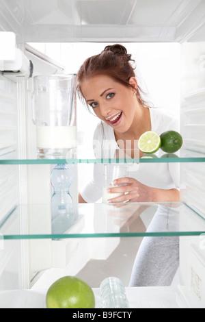 Portrait de jeune femme milkglass mettre au réfrigérateur et souriant