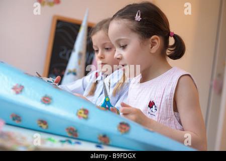 Profil de côté deux filles faire cône en carton Banque D'Images