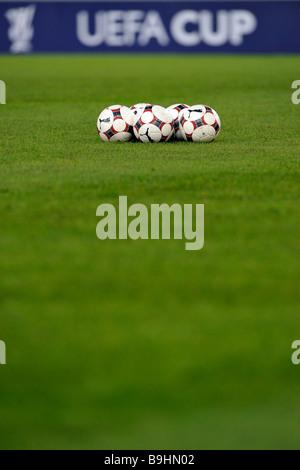 Ballons de football sur un terrain de football, en face de panneaux publicitaires avec le logo de l'UEFA-Cup