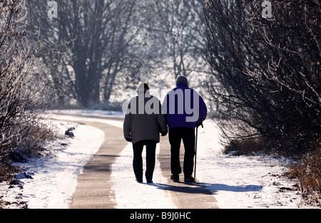 Couple de personnes âgées de prendre une marche en hiver Banque D'Images