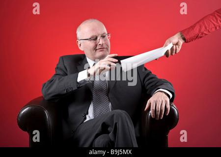 Un homme d'affaires documents donnant l'Assistant Banque D'Images