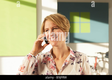 Woman using mobile phone in green loft Banque D'Images