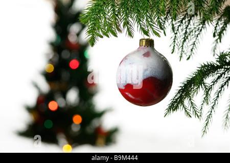 Gros plan d'une bille de verre rouge pendaison avec ornement de Noël floue on white