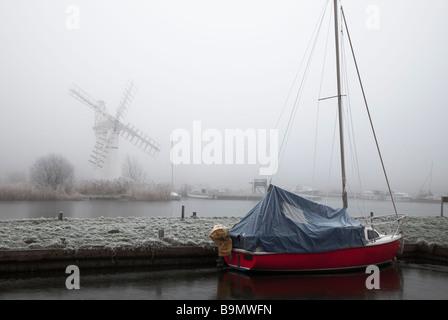 Thurne moulin se dresse dans la brume tandis qu'un voile rouge de l'avant-plan takács Banque D'Images
