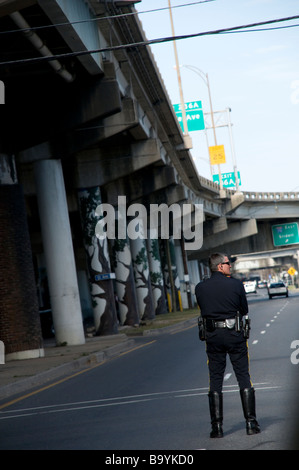 Agent de police de la Nouvelle Orléans en attente près de la I-16 près de la rampe Claiborne Avenue pour diriger Banque D'Images