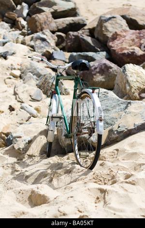 Une vieille bicyclette verte s'appuie contre une pierre sur une plage de sable fin à son propriétaire retour accueil Banque D'Images