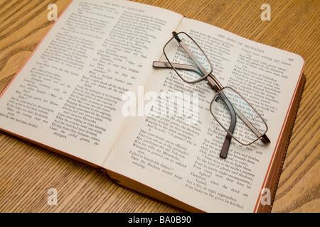 Une paire de lunettes de lecture reposant sur un livre de poèmes de Longfellow.