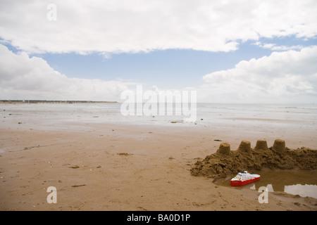 Un jouet bateau de croisière flotte dans les douves d'un château de sable sur une grande plage avec l'océan loin Banque D'Images
