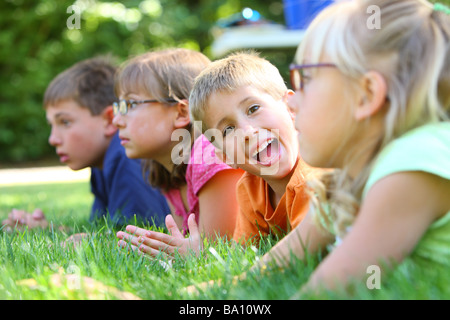 Groupe d'enfants laying in grass, un garçon attend at camera Banque D'Images
