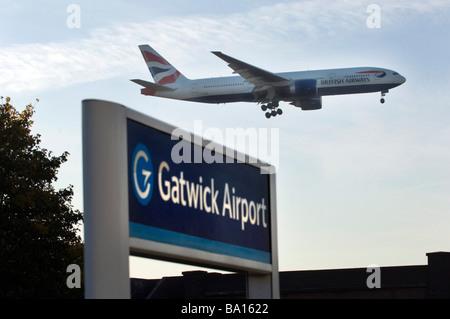 Les roues d'atterrissage sont vers le bas comme un British Airways Jet Airplane lands au-dessus de la gare à l'aéroport Banque D'Images
