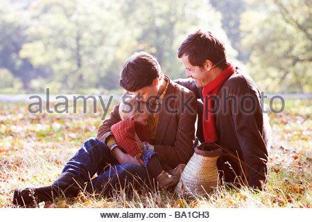 Une jeune famille assis sur l'herbe en temps d'automne Banque D'Images