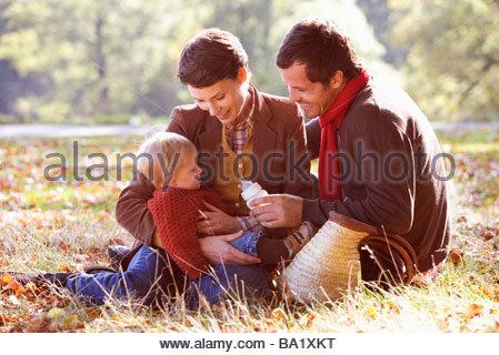 Une jeune famille assis sur l'herbe, père de l'enfant Banque D'Images