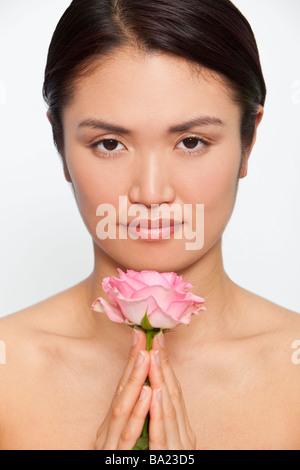 Portrait d'une belle jeune femme japonaise tenant une rose rose entre ses mains jointes tandis que dans la contemplation Banque D'Images