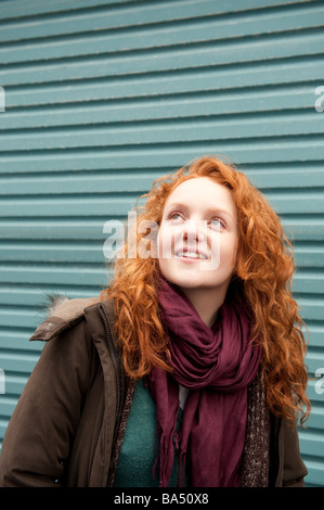 Happy red haired femme fille regardant vers le haut standing in front of blue metal porte, UK Banque D'Images
