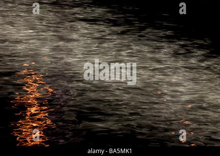 La lune et l'éclairage de rue réflexions dans l'eau de la rivière dans la nuit. Banque D'Images