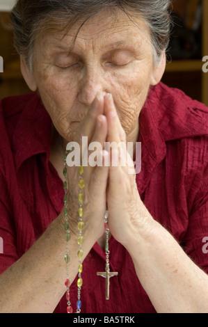 Une femme plus âgée priant son chapelet Banque D'Images