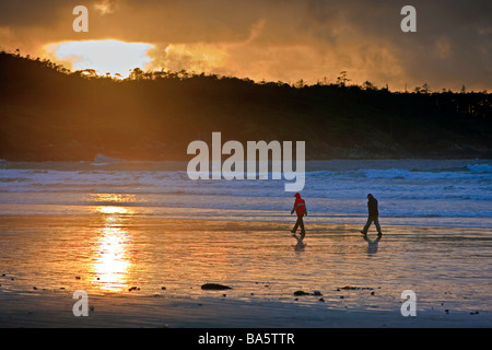 Couple en train de marcher le long de la plage de Cox Bay près de Tofino pendant le coucher du soleil une aire de Banque D'Images