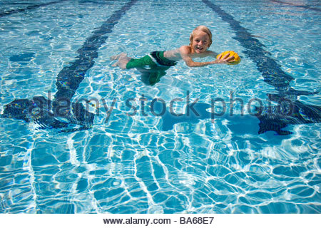 Young boy playing with ball in swimming pool Banque D'Images