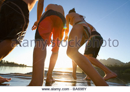 People Jumping off dock dans le lac Banque D'Images