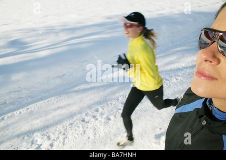 Deux femmes le jogging sur route enneigée, Styrie, Autriche Banque D'Images