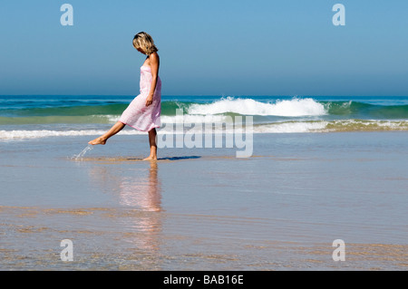 Jeune femme marchant le long de la plage des coups de l'eau Banque D'Images