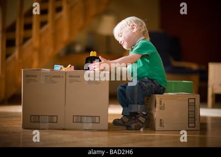 Enfant jouant avec des jouets sur des boîtes de carton