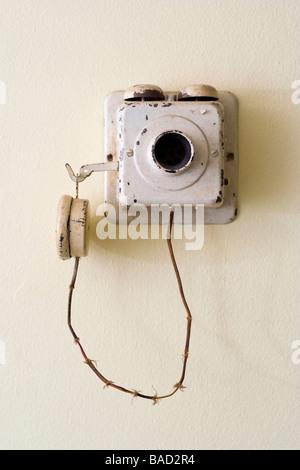Un antique téléphone accroché sur un mur jaune pâle. Banque D'Images