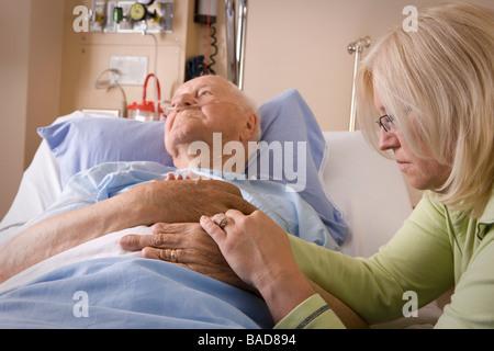 Un homme âgé et sa fille; Woman sitting by a man's hospital bed Banque D'Images