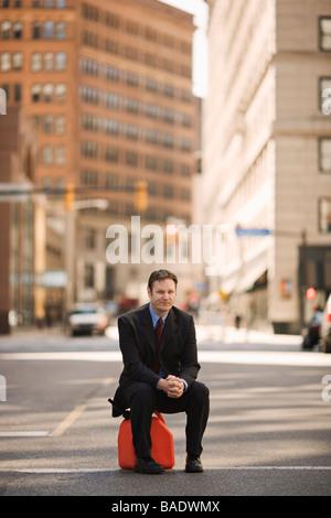 Businessman Sitting on gaz peut au milieu d'une rue de la ville Banque D'Images
