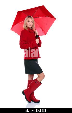 Belle jeune femme portant un manteau rouge et des bottes rouges de wellie umbrella isolé sur fond blanc Banque D'Images