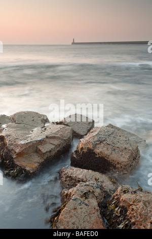 Vagues se briser contre les rochers du point de netteté à Tynemouth, éclairé par la lumière du printemps tôt le Banque D'Images