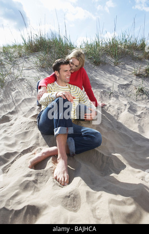 Couple sitting on beach, embracing Banque D'Images
