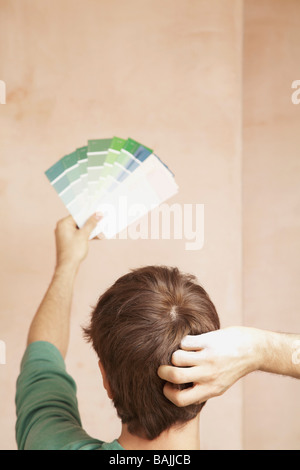 L'homme à la peinture en couleurs du nuancier, dans chambre non rénovées, vue arrière Banque D'Images