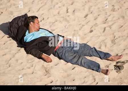 Un homme de prendre une sieste sur le sable à Huntington Beach, Californie Banque D'Images